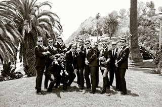 black-and-white-photo-of-groom-and-groomsmen-in-sunglasses-on-lawn-at-bel-air-bay-club-palm-trees