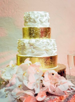 wedding-cake-with-gold-leaf-and-white-ruffles-next-to-phalaenopsis-orchids