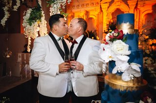 two-grooms-in-white-tuxedo-jackets-with-black-lapels-kiss-next-to-tall-blue-wedding-cake