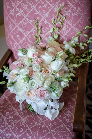 wedding-bouquet-white-and-pink-roses-and-tall-flower-accents-on-pink-upholstered-chair