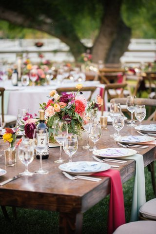outdoor-bohemian-wedding-reception-bare-wood-table-with-draped-pink-and-olive-cloth-napkins
