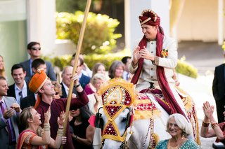 indian-wedding-tradition-groom-in-sherwani-and-turban-on-horse-for-baraat-in-los-angeles