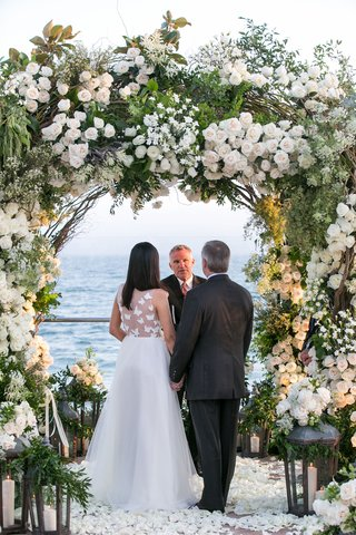 santa-barbara-vow-renewal-wedding-green-neutral-color-palette-white-flowers-arch-design-flower-petal