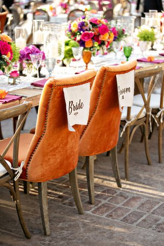 wedding-reception-colorful-boho-chic-outdoor-orange-nailhead-velvet-chairs-head-table-wood-seating