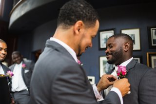 groomsman-fixes-grooms-pink-rose-boutonniere