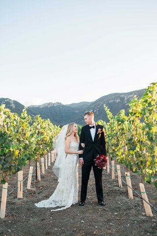 bride-in-jim-hjelm-wedding-dress-and-groom-stand-in-vineyard-vines-california-red-bouquet-of-flowers