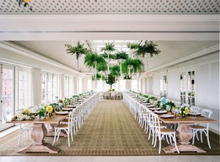 wedding-reception-sunlit-ballroom-two-long-wood-tables-ferns-in-macrame-planters-hanging-ceiling