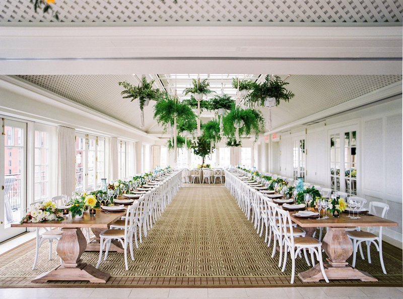 wedding reception with low centerpieces greenery wood table