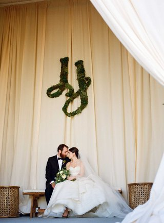 bride-and-groom-at-rustic-wedding-greenery-sculpture-in-monogram-wall-art-on-drapery