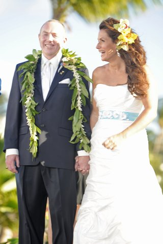 newlyweds-smile-at-ceremony-in-hawaii-with-leis