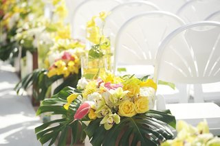 white-ceremony-chairs-and-jungle-leaf-decorations