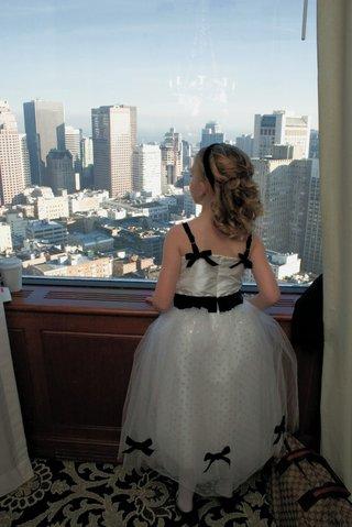 flower-girl-in-white-and-black-dress-looks-at-san-fran-skyline