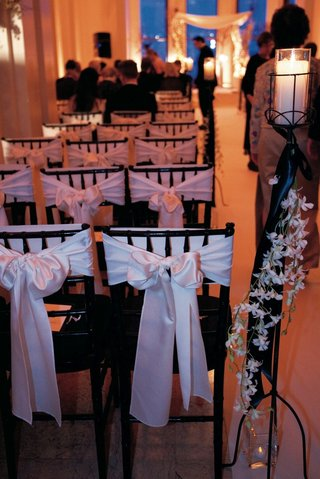 white-bows-around-black-ceremony-chairs