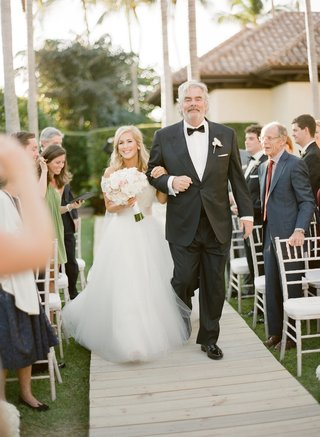 bride-walks-down-wood-plank-aisle-with-father-of-bride-at-home