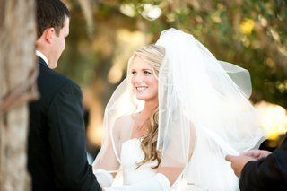 bride-at-ceremony-with-white-satin-trim-veil