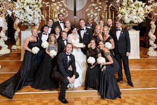 bride-in-lazaro-ball-gown-bridesmaids-in-mismatched-black-dresses-junior-bridesmaid-groomsmen-tux