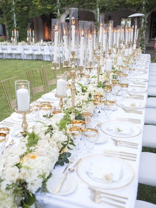 white-gold-and-green-color-scheme-tall-candlebras-adding-warmth-to-dinner-under-the-stars