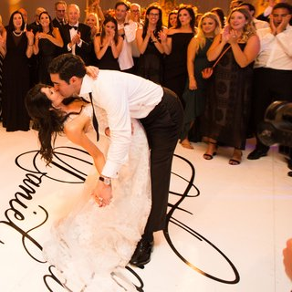 wedding-reception-bride-and-groom-dip-and-kiss-during-first-dance-on-personalized-dance-floor-names