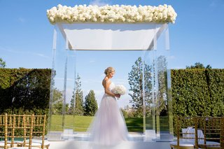 bride-in-strapless-wedding-dress-and-white-bouquet-standing-under-lucite-acrylic-clear-ceremony-arch