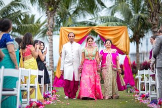 indian-american-bride-in-pink-and-turquoise-lehenga-walks-down-the-aisle-with-parents