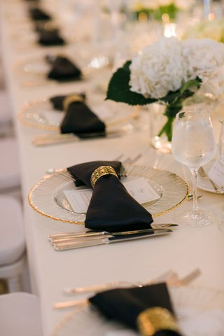 wedding-reception-long-table-white-linen-gold-charger-black-napkin-bow-with-gold-napkin-ring