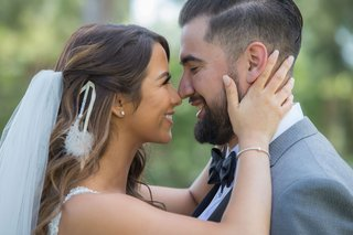 bride-holding-groom-face-and-touching-nose-eskimo-kisses-bride-with-veil-and-feather-hair-accessory