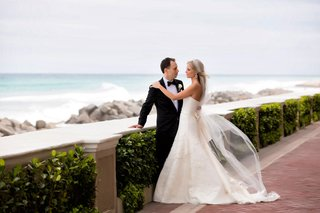 bride-in-strapless-vera-wang-wedding-dress-and-veil-with-groom-in-tuxedo-looking-over-beach