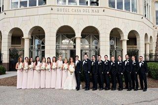 wedding-party-pink-bridesmaid-dresses-groomsmen-in-tuxedos-in-front-of-casa-del-mar-in-santa-monica