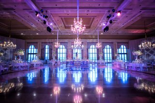 wedding-reception-set-up-at-the-breakers-ballroom-purple-lighting-chandeliers-candelabra-white