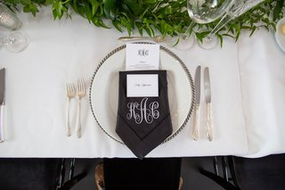 wedding reception place setting silver charger plate black napkin monogram greenery