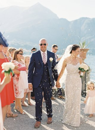wedding-guests-tossing-confetti-flower-petals-as-bride-and-groom-arrive-to-reception-venue-lake-como