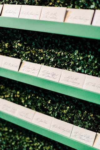 wedding reception hedge wall of greenery with calligraphy escort cards on green shelf