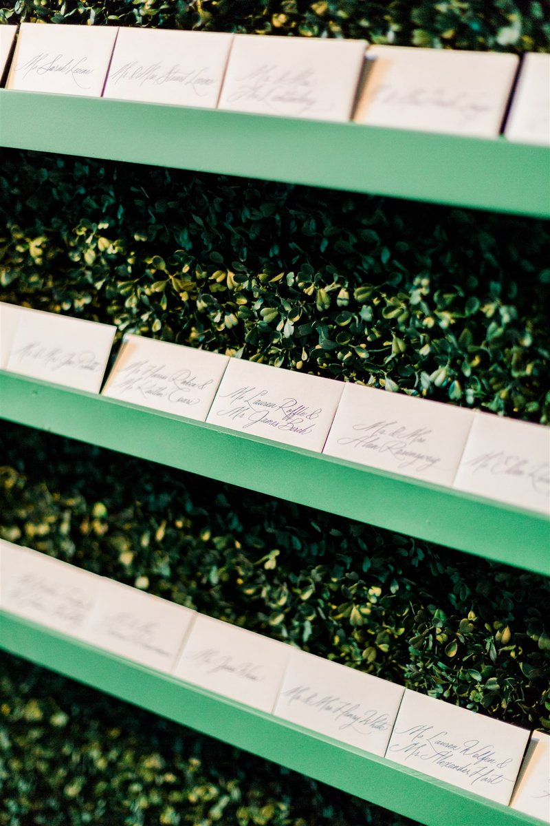 Escort Cards on Wall of Greenery