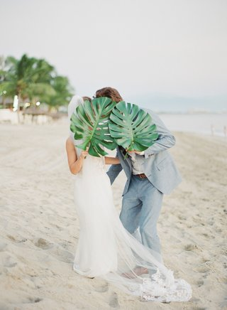 bride-and-groom-wedding-portrait-on-beach-in-sand-with-tropical-palm-leaves-jungle-style