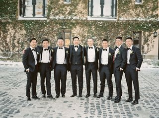 oheka-castle-wedding-groom-in-tuxedo-and-vest-with-groomsmen-in-suits-black-bow-ties-boutonnieres