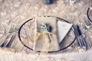 wedding-reception-table-linen-with-rimmed-charger-plate-rosette-texture-tablecloth-ribbon-napkin