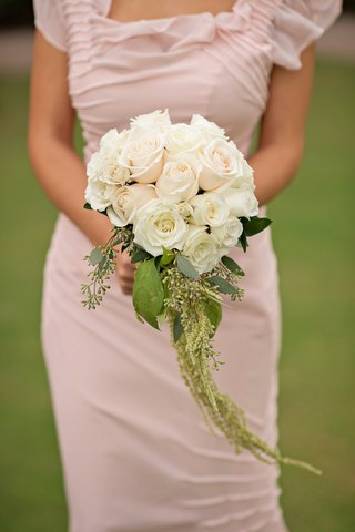 bridesmaid-in-pink-dress-holding-white-rose-and-light-pink-bouquet