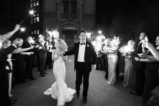 black-and-white-photo-of-bride-in-strapless-mermaid-dress-and-groom-in-tux-sparkler-exit-tunnel