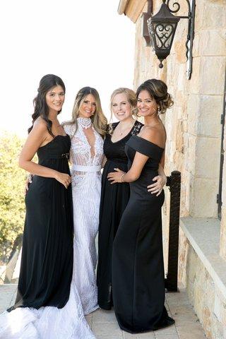 bride in high neck plunging neckline wedding dress sash bridesmaids in mismatch black gowns