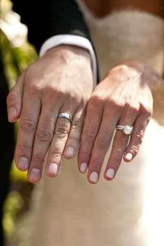 bride-and-groom-show-their-wedding-rings-bands-diamonds-nails-manicure