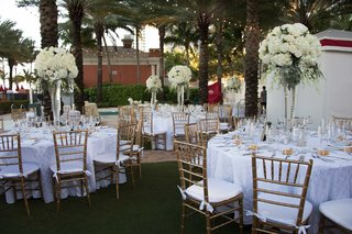 wedding-reception-with-round-white-tables-gold-chairs-tall-centerpieces-rose-hydrangea-flowers