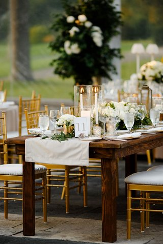 wedding-reception-clear-tent-dark-wood-table-gold-chairs-linen-runner-garland-taper-candles