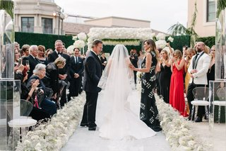 bride-in-veil-and-oscar-de-la-renta-wedding-dress-with-father-mother-guests-watching