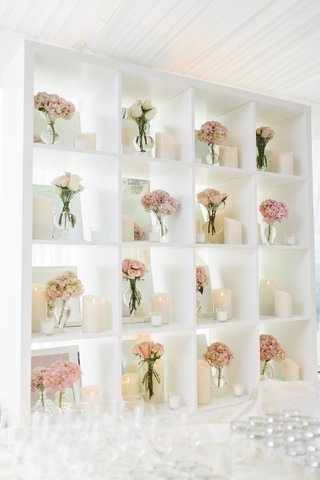 bookcase-behind-wedding-bar-with-pink-clusters-of-flowers-in-bud-vases-and-pillar-candles