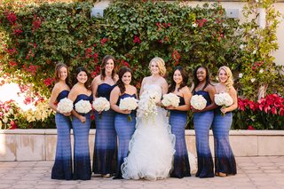 bride-in-demetrios-bridesmaids-in-betsey-and-adam-dresses-in-shades-of-blue