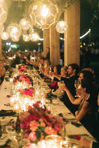wedding-reception-outdoor-table-glass-orb-lantern-pendant-lights-low-pink-centerpiece-toasts-cheers