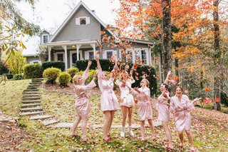 bride-and-bridesmaids-dressed-in-pink-and-white-robes-throw-fall-leaves-into-their-air-outside