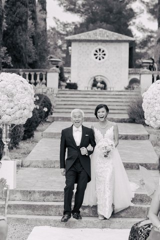 black-and-white-photo-of-bride-and-father-of-bride-walking-toward-aisle-outdoor-venue-in-france