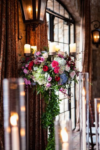 metal-candelabra-wedding-centerpiece-with-greenery-pink-red-roses-blue-hydrangeas