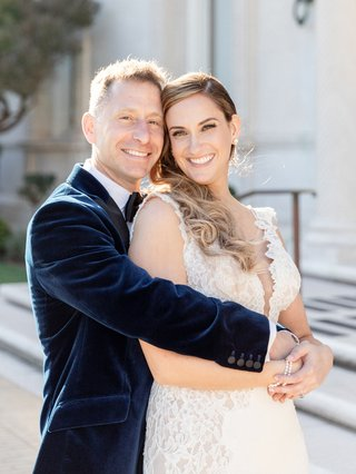 groom-in-navy-velvet-suit-jacket-hugging-bride-in-pnina-tornai-from-behind